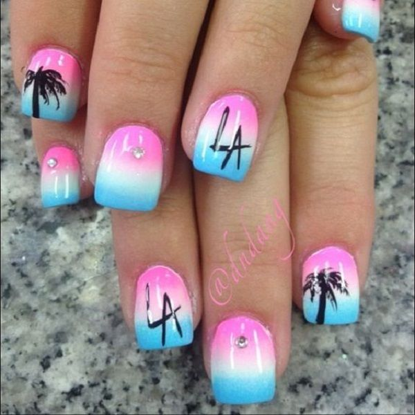 Pretty looking Palm Tree Nail Art design. A combination of gradient colors in white, blue and pink are painted on the nails. The design is topped off by black silhouettes of palm trees and typography.
