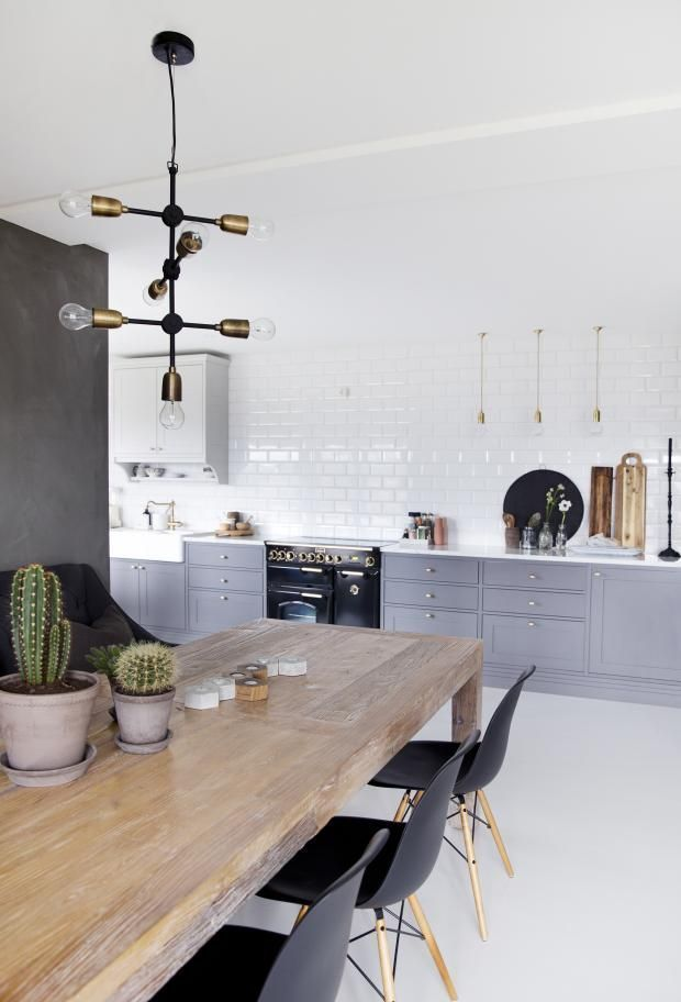 modern industrial kitchen with gray cabinets and mid century modern chairs