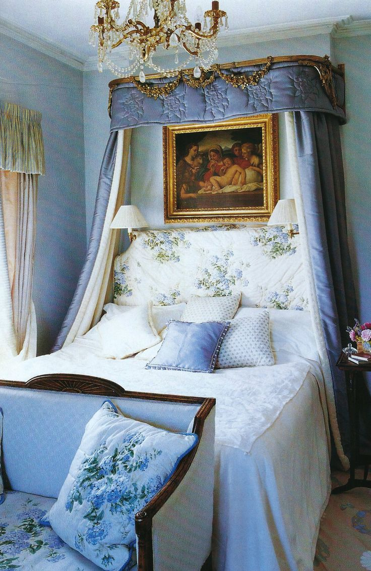 French toile with an antique settee at the foot of the bed w/a padded headboard and drapery canopy.