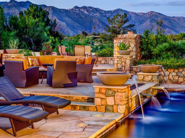 Designer Lori Carroll created a beautiful and relaxing outdoor living space with natural stone surrounded by lush landscaping. The pool area is equipped with plenty of seating options, making it the perfect place for both relaxing and entertaining.