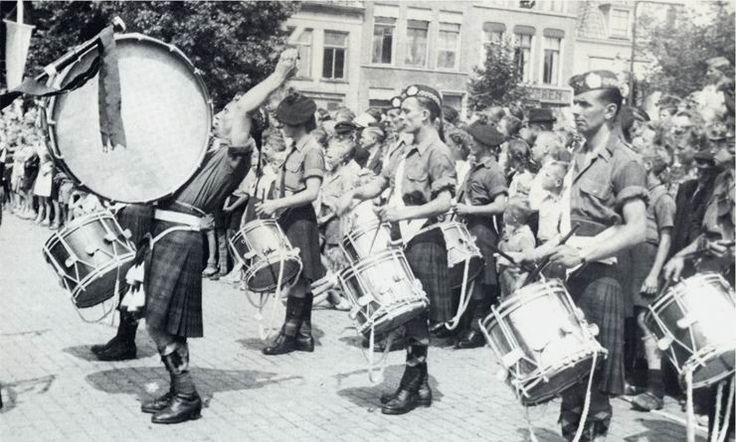 The combined (5th. Canadian Armoured Division) pipe bands of the Irish Regiment and Cape Breton Highlanders of Canada playing for the march-past of the B.S. who turned in their arms and were then disbanded.