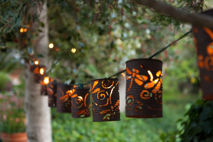24 Unique Beautiful DIY Garden Lanterns - 12. OLD RUSTY TIN CANS PERFORATED TO EXUDE LIGHT