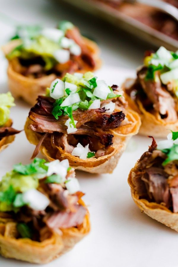 Mini tortilla cups filled with crockpot carnitas and topped with guacamole, onion, and cilantro! Perfect for game day!