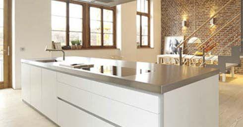wit kookeiland met betonnenblad contrasteert mooi met houten kozijnen