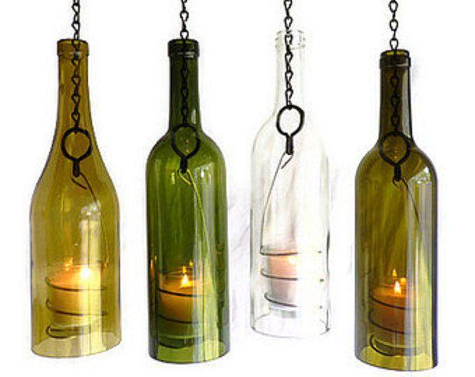 Lot de 3 lanternes ouragan accrochantes !  Vert, or et Olive brun 750 ml. vin bouteilles en verre. Belles couleurs et bon verre épais. coupe flamme et méticuleusement main poncé dans une étape 3 processus pour un bord lisse parfait. La main de fil spirale conçu détient un verre votif. Collerette métallique solide permet une chaîne en métal noir qui est agrémenté dun plus grand lien de boucle en métal pour accrocher facilement. Chaînes de suspension sont à 3 longueurs différentes pour donner…
