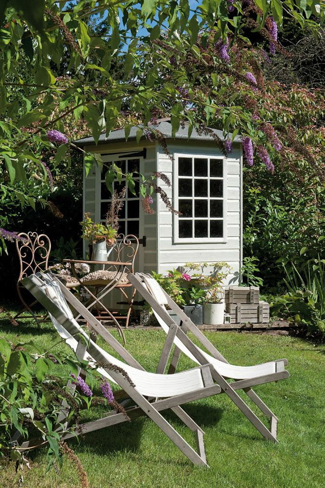 Summerhouse and deck chairs in a lush country garden.
