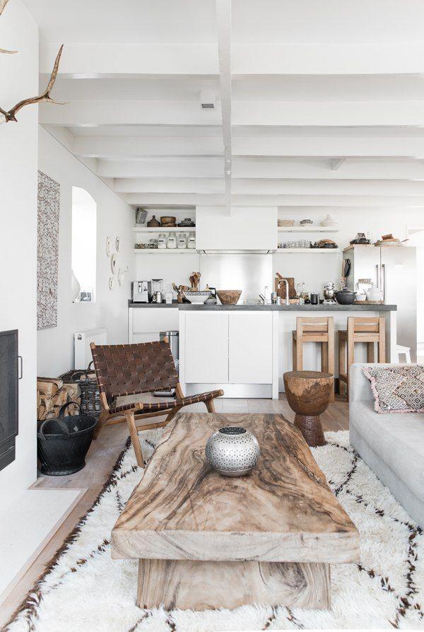 Ambiance ethnique chic dans ce salon contemporain, table basse en bois, tapis esprit boucherouite et murs peints en blanc.