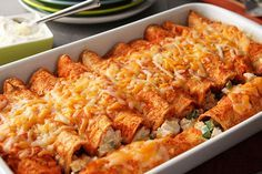 Got leftover cooked chicken? Roll it up in tortillas with peppers and cream cheese, then top with red sauce and garlicky sour cream to make these tasty enchiladas.