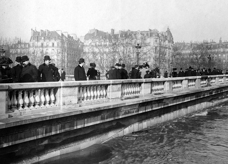 La gran inundación de París en 1910.El agua no para de subir mientras muchas personas observan desde el Puente del Alma. BHVP, Roger Viollet Multitud de personas reunidas en los puentes y terraplenes contemplan en silencio como el río arrastra muebles, barriles, cadáveres de animales, barcazas y restos de lo que había destrozado a su paso en una loca carrera hacia el mar.
