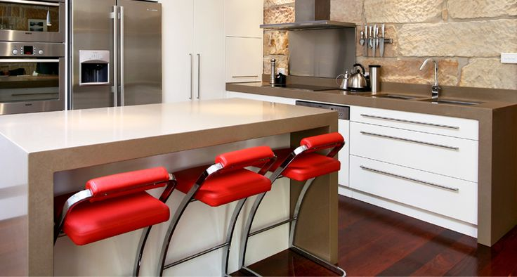 Spot of the day - White kitchen personalised with ‪Caesarstone‬ Shitake (4230) worktops and island and striking bright red bar stools. Lovely.