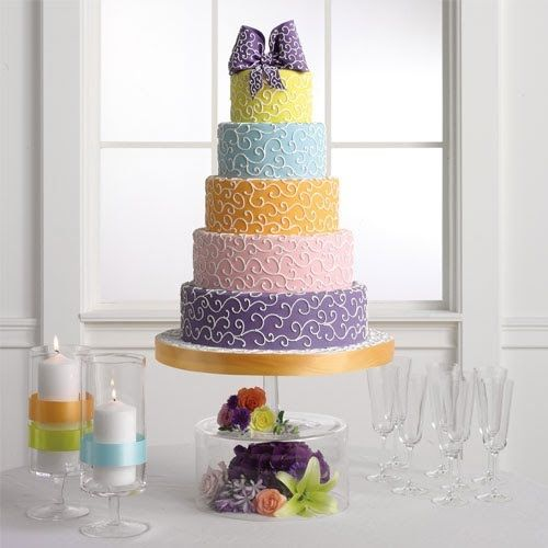 Round wedding cake with five ties, each in a different pastel color and covered with white swirls and a dark blue swirl covered bow as a cake topper.