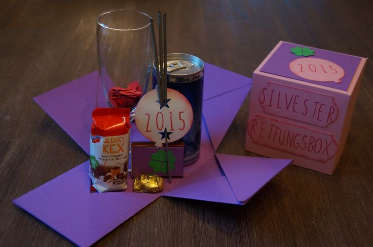 Silvester-Rettungsbox mit Sektglas, Prosecco, Schokoschwein, Glückskex, Wunderkerzen und Streichhölzern.