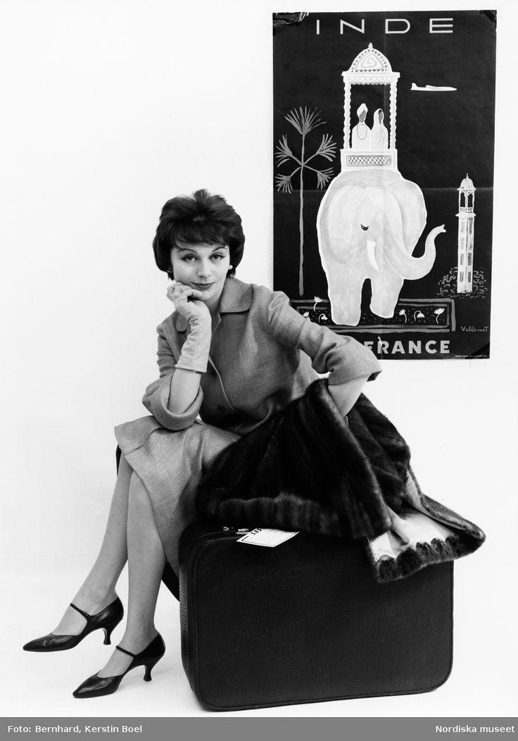 Modell i dräkt och handskar, pälsjacka och resväska i handen. Plansch i bakgrunden av Bernard Villemot, Air France Inde. Fotograf: Kerstin Bernhard, ca 1955-1960