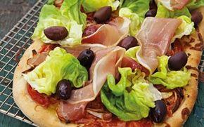 Pizza med skinke, salat og oliven Hjemmelavet pizza med tynd, sprød bund og bl.a. ost og solmodne tomater. Den er hele arbejdet værd.