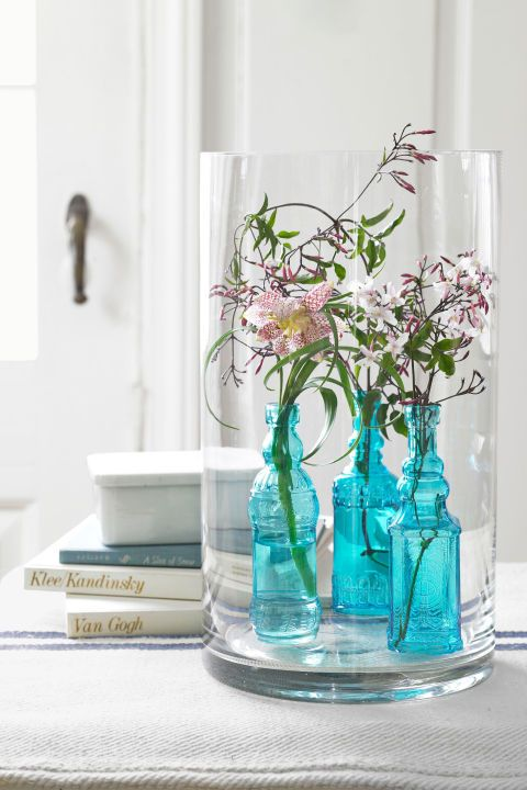 Display Vintage Bottles:  A few stems of jasmine arranged in vintage blue apothecary bottles can be placed inside a larger glass cylinder for a stylish and special centerpiece.