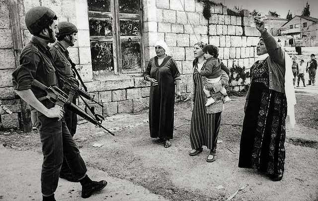 Confrontation – Jabalia Camp, Gaza Strip, Palestine    1988    The women are complaining about the arrest and mistreatment of stone throwing Palestinian young boys. It became official policy, during this period, for the army to break the arm and leg bones of any boy caught throwing stones at military personnel.    Shortly after this shot was taken the women were dispersed using baton charges and tear gas.
