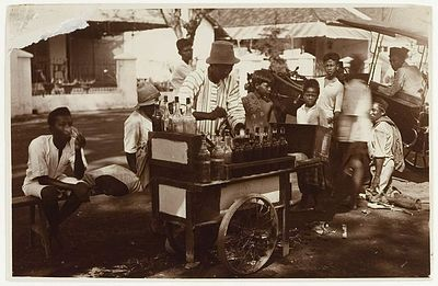 Pedagang Limun terlihat sedang melayani pembeli di Makasar pada tahun 1915 menggunakan gerobak yang didorong