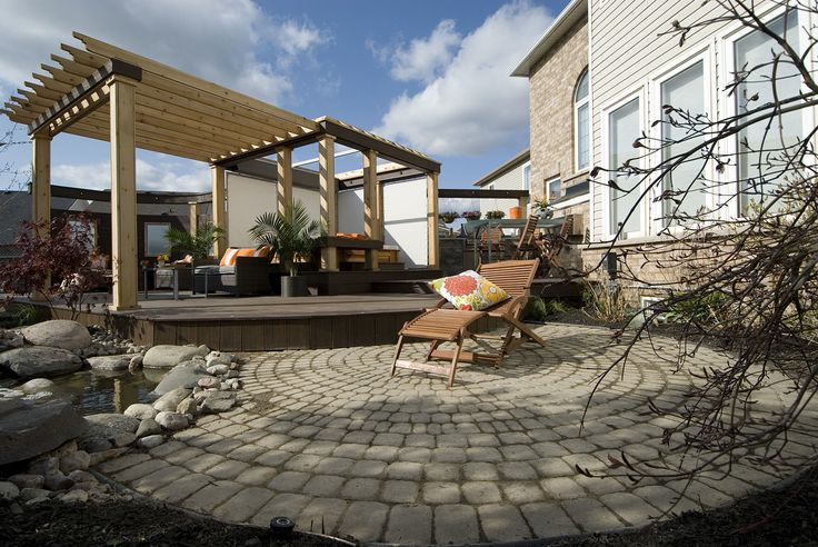 """This design harmonizes with the homeowner's existing interlock stone patio.  From """"Decked Out"""" project """"The Round Square Deck"""".  Deck Design by Paul Lafrance Design."""