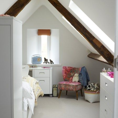 A split level teenager's bedroom in the attic has built-in joinery doubling as a headboard and innovative storage to allow the bed to face the view. Design by Pippa Paton Designs