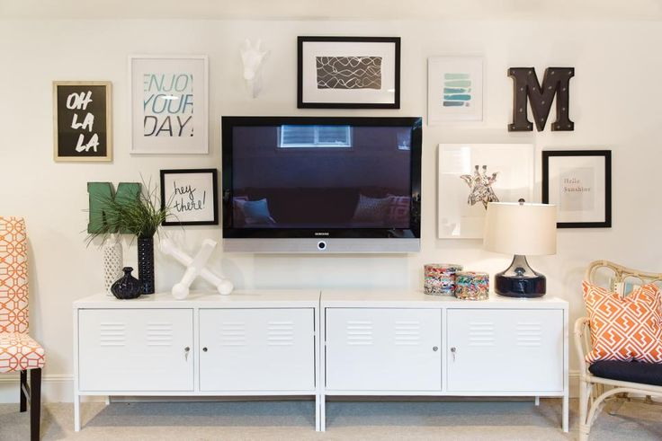 An asymmetrical gallery wall loaded with inspirational sayings, family initials, graphic sketches and giraffes brings lightness and fun to this eclectic playroom. Retro locker-inspired cabinets almost disappear against the white wall, keeping the space from feeling too busy.