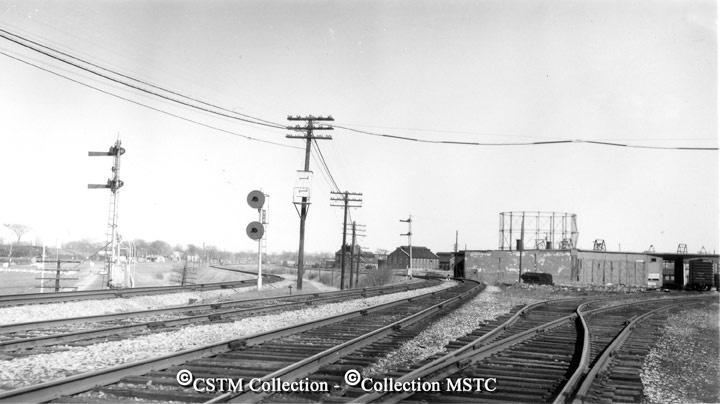 """Location: Ottawa East, ON  Railway Name: CANADIAN NATIONAL RAILWAYS  Date: 1965-00-00  Caption: """"Scenes around the Mann Avenue shops, from1932 until their demise in 1966. View of Mann Ave shops, with the CPR main line in the far left, the CNR centre tracks, those on right diverge to Bank st. yard. Taken in the spring."""""""