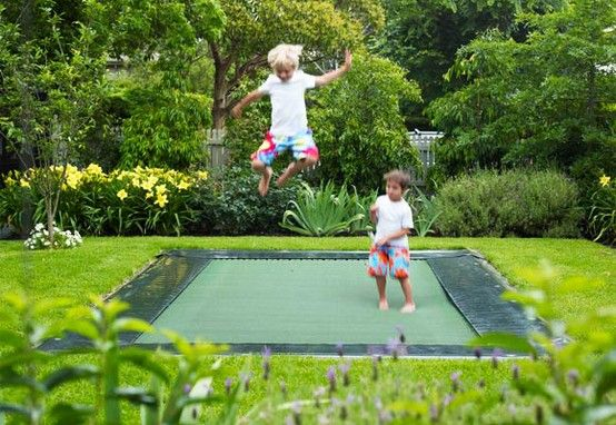 this idea of an in-ground trampoline is just too wonderful -- no need for the net around the sides and it looks so much better.