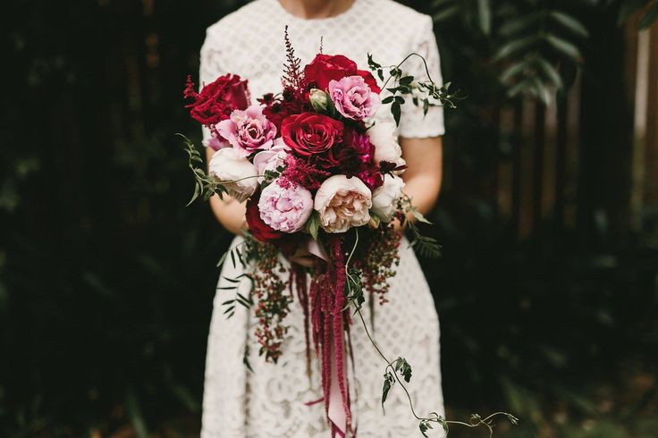 Pink, peach, red and plum bridal bouquet by Shady Fig using David Austin roses, peony roses, tulips, peppercorn and amarnthus. Photographed by Zoe Morely