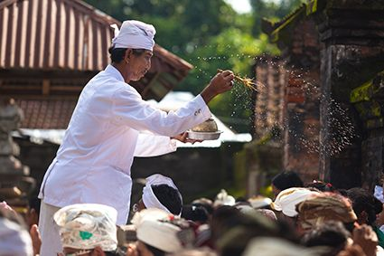 Balinese Hindu priest performing blessing with holy water