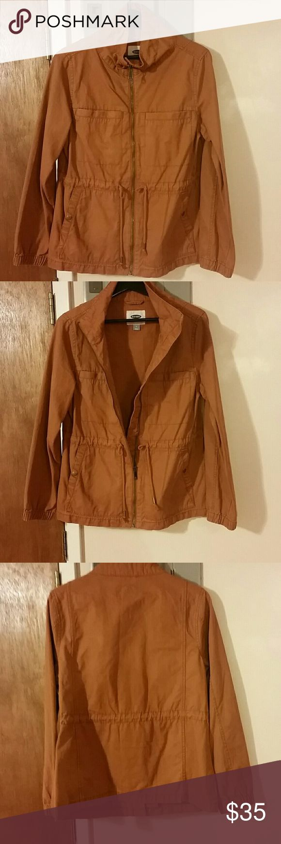 OLD NAVY utility jacket Worn once to run to the store, this jacket will no longer serve me as winter is upon us in NY. The jacket is in perfect condition. It's a beautiful rust, pumpkin color. It has adjustable cords at the waist, zipper down the front and stretch cuffs. There are two open pockets at the chest, deep enough for cell phone, keys, etc. There are two snap closure pockets on the bottom (front) for securing other items. This jacket is 100% cotton and machine washable. Old Navy…