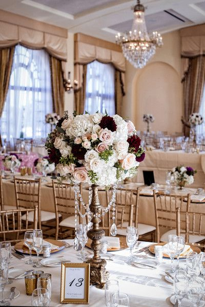elegant indoor ballroom wedding reception decor tall pastel pomander centerpieces with roses hydrangeas