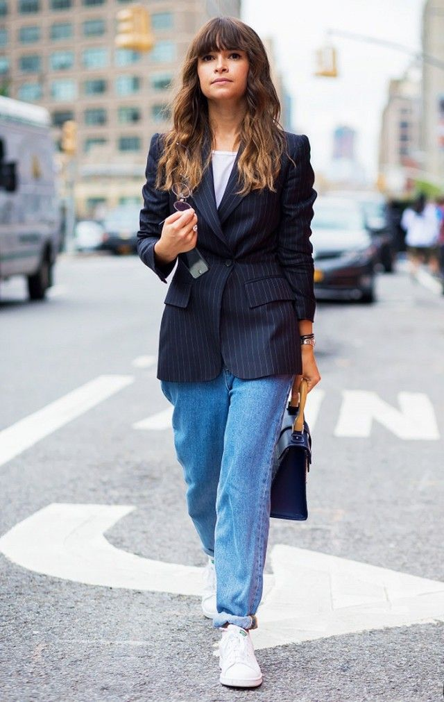 Miroslava Duma wears a t-shirt, pinstripe blazer, cuffed jeans, sneakers, and a top-handle bag