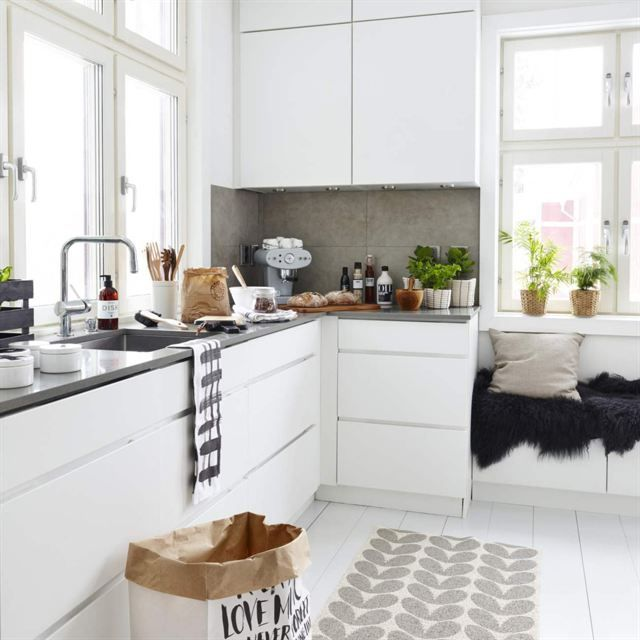 Stilrent kök i vitt. Köksinredning från Kvik. Matta, Brita Sweden. Pappåse, Love warriors. Svart fårskinn och rutiga handdukar från Åhléns.