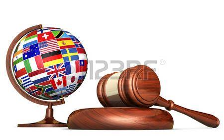 Los sistemas internacionales de derecho, la justicia, los derechos humanos y el concepto de la educación de negocios global con banderas del mundo en un globo de la escuela y un martillo en un escritorio aislado en el fondo blanco.