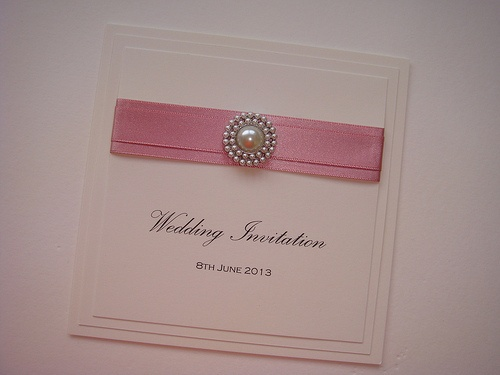 Flat wedding invitation with satin ribbon and a pearl embellishment. Shown in pink