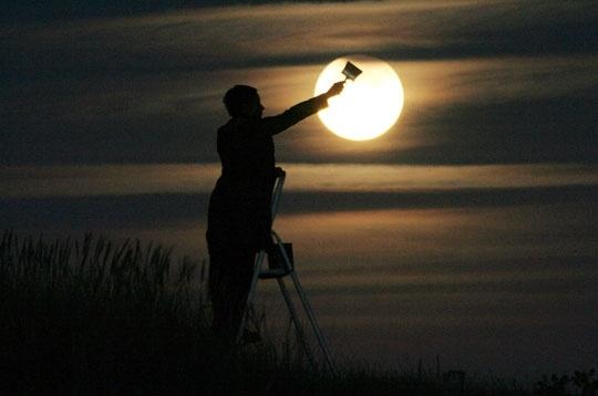 """""""A l'occasion d'une éclipse partielle de lune, une partie de notre satellite est plongée dans l'obscurité. Sabine, juchée sur un escabeau, fait mine de peindre la lune en noir à l'aide d'un pinceau."""" Plage de Tréguennec, Finistère, août 2006, FRANCE"""
