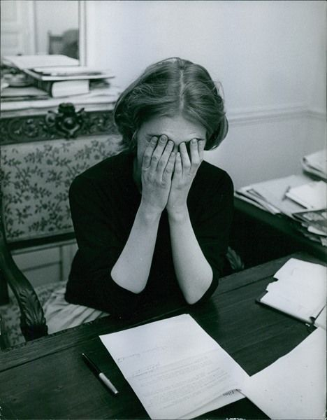 Vintage photo of Marie-Jeanne Bardot siting and covering her face. -
