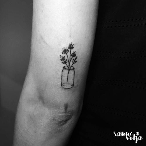 Wild flowers in a bottle tattoo on the tricep. Tattoo artist:...