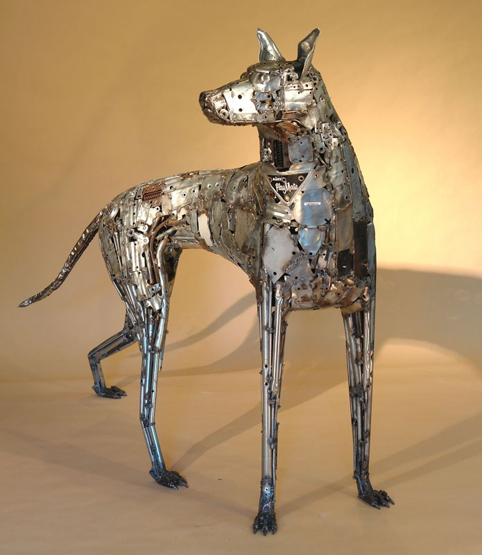 Ajay - NDI Gallery  Dog sculpture created from a variety of found metals including galvanized parts from old pull golf carts. Tubing, hand flattened stock, hinges and various other steel scraps.   By Brian Mock
