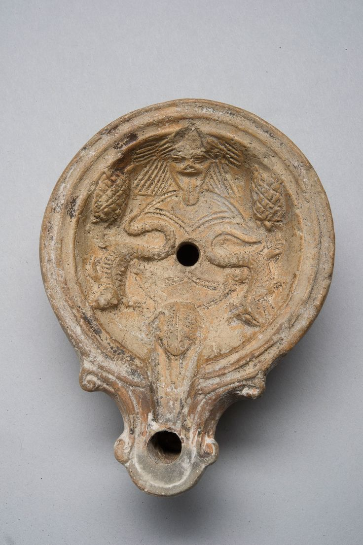 "As well as Gorgoneion, this Roman oil-lamp has other apotropaic elements: 2 turtles, 2 lizards & a frog. ""Lizards, frogs and other reptiles were also associated with the Underworld: lizards symbolized death & resurrection because of their hibernation habits, while turtles were dear to the god Mercury ... The plethora of chthonian animals represented on this lamp echoes & magnifies the power of the Gorgon, making this object both a device for lighting & a potent talisman against the evil…"