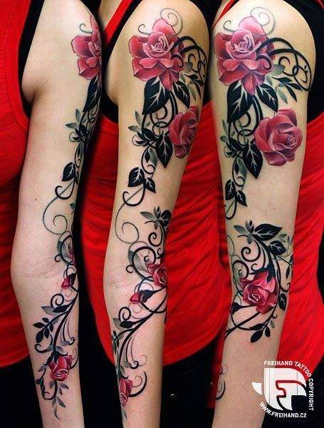 A red woman with cool tattoos of flowers on her arm, pink flower