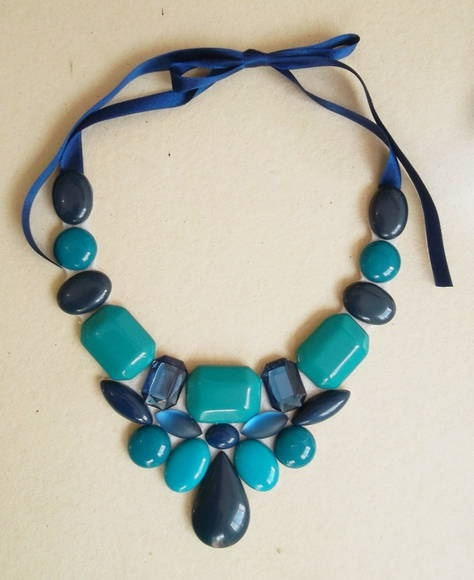 Maxi colar confeccionado com chatons nas cores turquesa e azul marinho.  Base em feltro na cor nude.  Fecha com fitas de cetim, sendo portanto de comprimento regulável. R$ 70,00