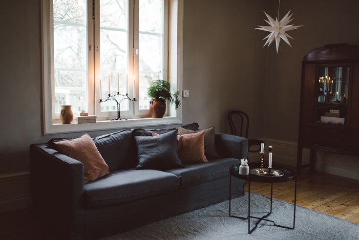 Moody holiday decor   candles and seasonal greenery add a festive touch  dark grey linen sofa   IKEA Karlstad sofa with a Bemz Loose Fit Urban cover in Medium Grey Rosendal linen   styling Babes in Boyland