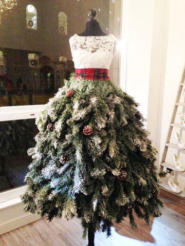 Um manequim é usado como a base desta árvore inusitada. No topo, uma blusa branca rendada e um cinto xadrez vermelho – duas cores principais do Natal. Um tipo de árvore de Natal preenche o espaço da saia, que leva pinhas.