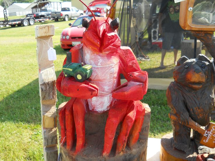 A chainsaw carved lobster sitting down hold tractor at