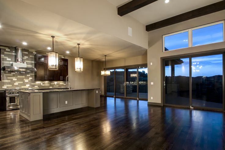 A wide open floor plan with layered ceiling heights create defined yet fluid dining, living and kitchen spaces.