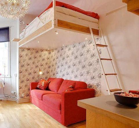 O papel de parede florido romantiza com o vermelho do sofá e da roupa de cama, acima.