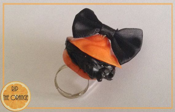Lovely Macaron in orange with black satin ribbon on top. Black Whipped cream with crystal.  Shaped macaron version  Piece measure around 3 - 4cm