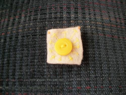 embroidery of a sun with button center on 1x1inch felt