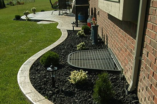Landscaping around window well and pipes back yard for Window design cement