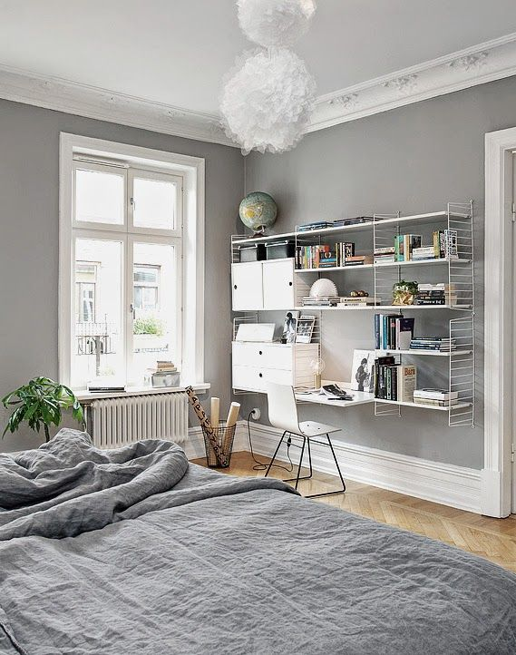 Workspace/study/office in the bedroom: white String shelving system, grey walls, white pendant light, grey bed linen, herringbone floor, tall skirting boards, ornate cornices